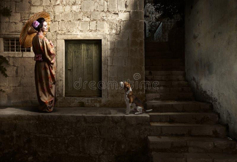 Härlig kvinna i kimono med paraplyet och den gulliga hunden arkivfoto