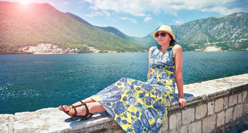 Härlig kvinna i klänning och hatt på kust av ön Boka Kotorska Montenegro arkivfoton