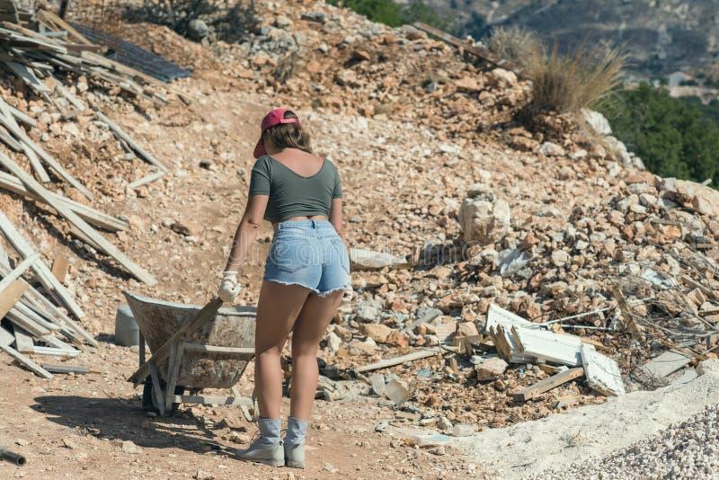 Härlig kvinna i kortslutningarna och i det röda nådde en höjdpunkt locket med en skottkärra för cement fotografering för bildbyråer
