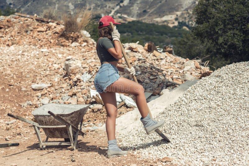 Härlig kvinna i kortslutningarna och i det röda nådde en höjdpunkt locket som hårt arbetar på konstruktionsplatsen royaltyfri fotografi