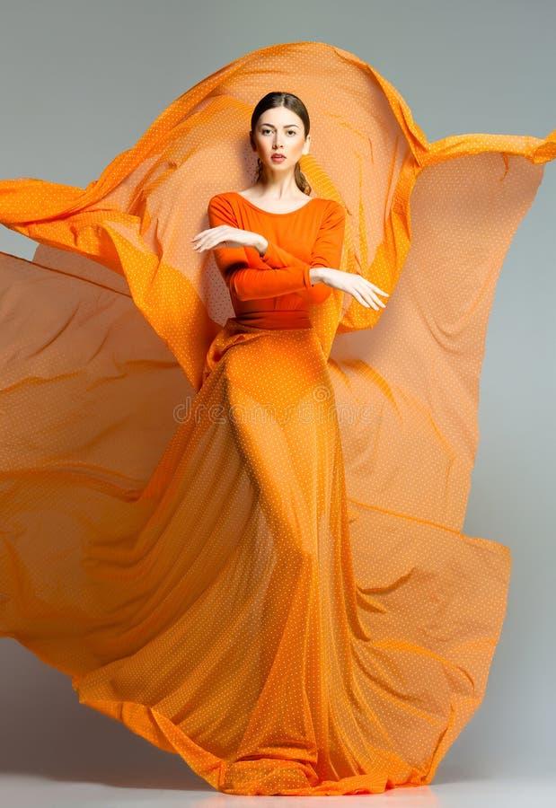 Härlig kvinna i långt orange posera för klänning som är dramatiskt royaltyfria bilder