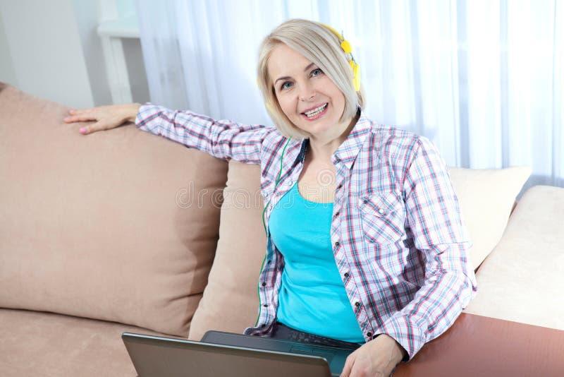 Härlig kvinna i ljus dräkt som hemma tycker om musik arkivfoton
