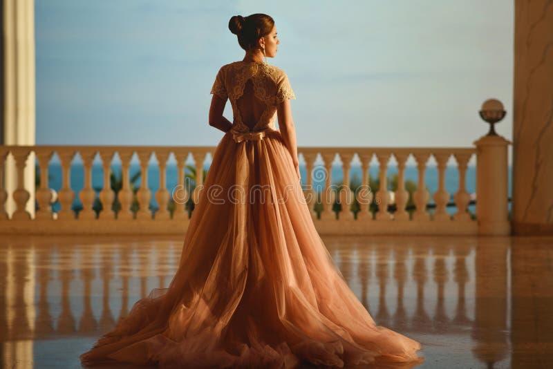 Härlig kvinna i lyxig balsalklänning med tyllkjolen och spets- bästa anseende på den stora balkongen med havssikt arkivfoto