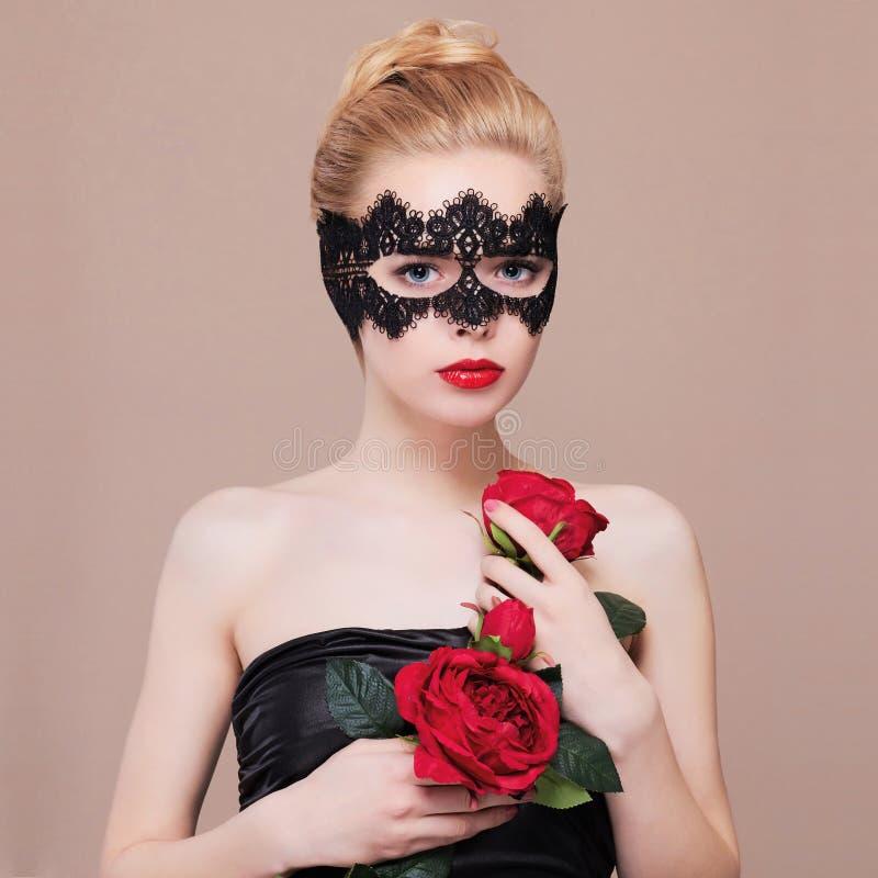 Härlig kvinna i maskeringsinnehavblommor royaltyfri fotografi