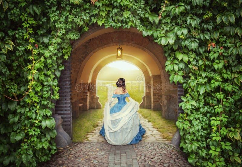 Härlig kvinna i medeltida klänning på den mystiska vägen royaltyfri fotografi