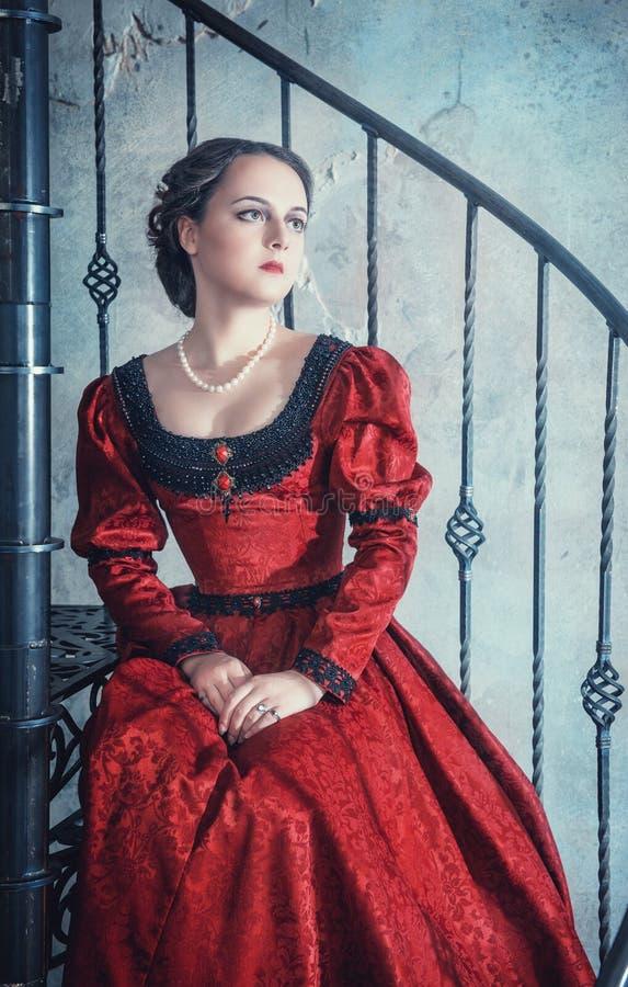 Härlig kvinna i medeltida klänning på trappan fotografering för bildbyråer