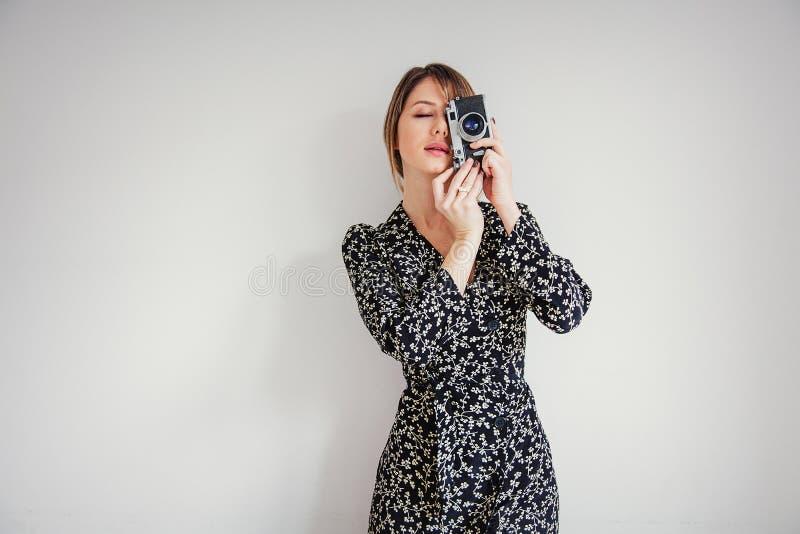 Härlig kvinna i moderiktig klänning med tappningkameran royaltyfri foto