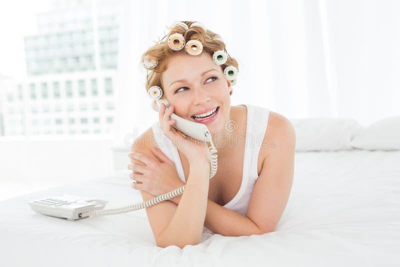 Härlig kvinna i papiljotter genom att använda telefonen i säng arkivfoton