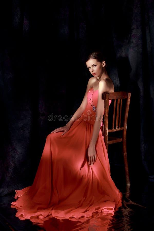 Härlig kvinna i röd aftonklänning på mörk bakgrund fotografering för bildbyråer
