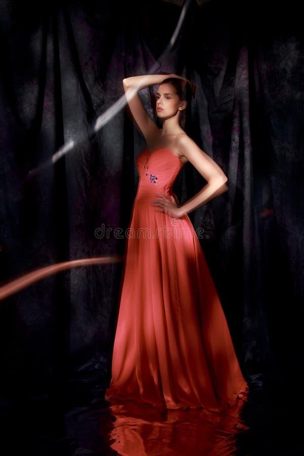 Härlig kvinna i röd aftonklänning på mörk bakgrund royaltyfria foton