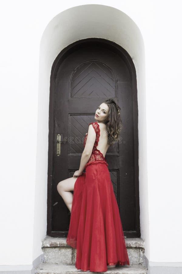 Härlig kvinna i röd klänning arkivfoto