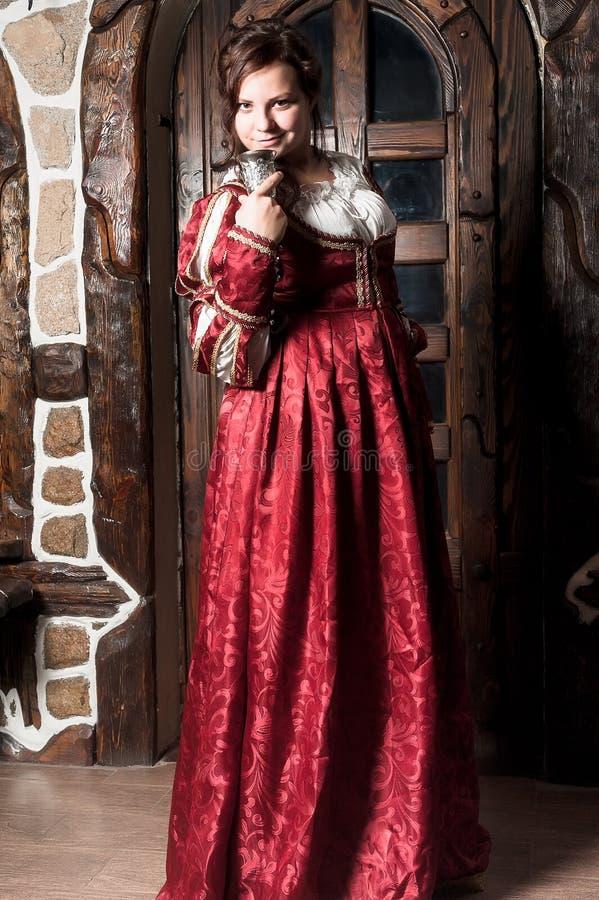 Härlig kvinna i röd klänning i retro barock royaltyfri fotografi