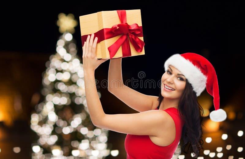 Härlig kvinna i röd klänning med julgåvan arkivfoto