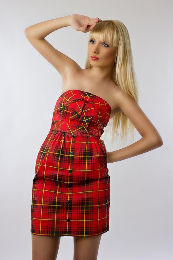 Härlig kvinna i röd klänning med långt hår royaltyfria foton