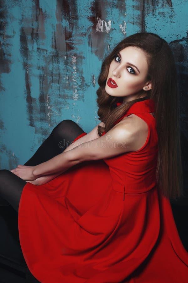 Härlig kvinna i röd klänning med lockigt hår fotografering för bildbyråer
