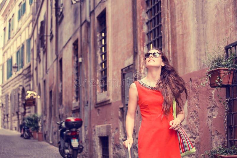 Härlig kvinna i röd sommarklänning som går att le i Rome, Italien royaltyfri bild