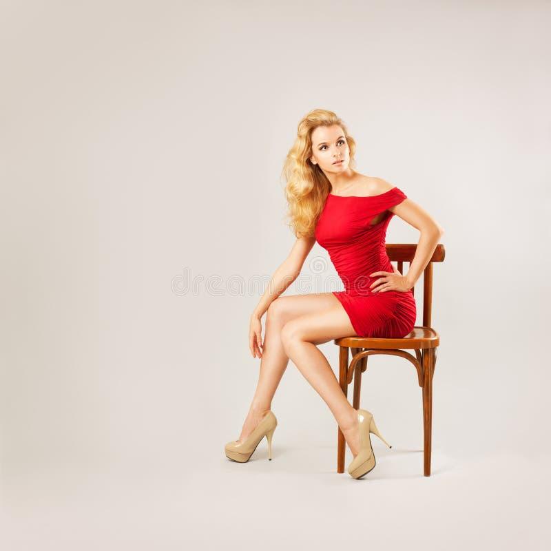 Härlig kvinna i rött klänningsammanträde på en stol royaltyfri fotografi