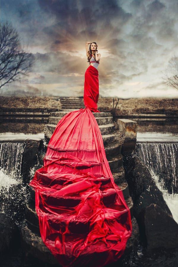 Härlig kvinna i rött långt klänninganseende på en vattenfall royaltyfri bild