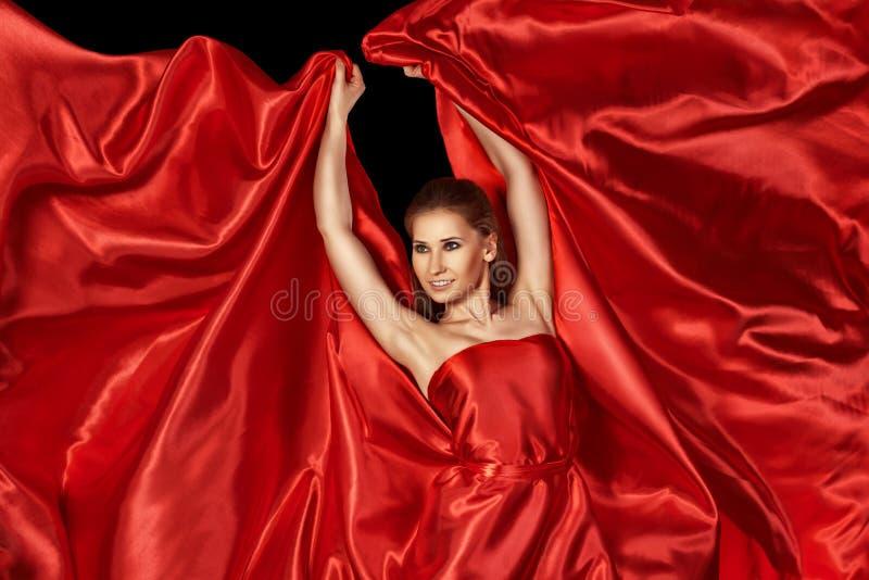 Härlig kvinna i rött siden- klänningflyg royaltyfri foto