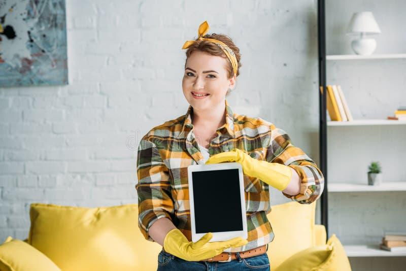 härlig kvinna i rengörande handskar som visar minnestavlan arkivbild