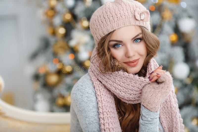 Härlig kvinna i rosa hatt nära julgranen royaltyfri fotografi
