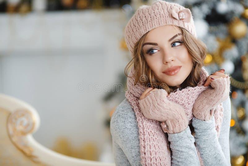 Härlig kvinna i rosa hatt nära julgranen royaltyfri bild