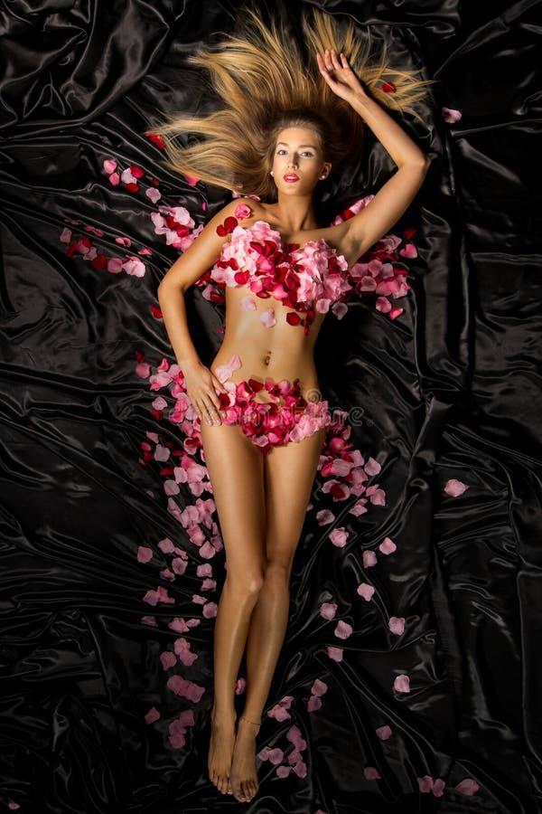 Härlig kvinna i rosa kronblad arkivbilder