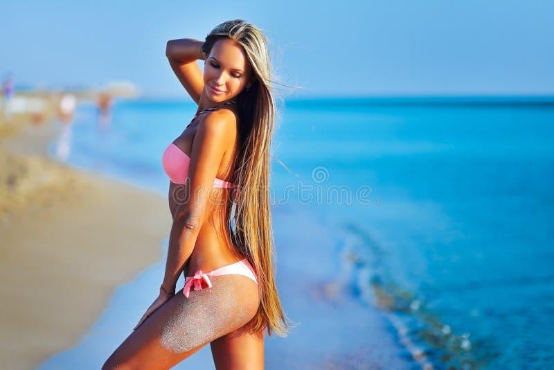 Härlig kvinna i sexig bikini som kopplar av på sommarstranden arkivbilder