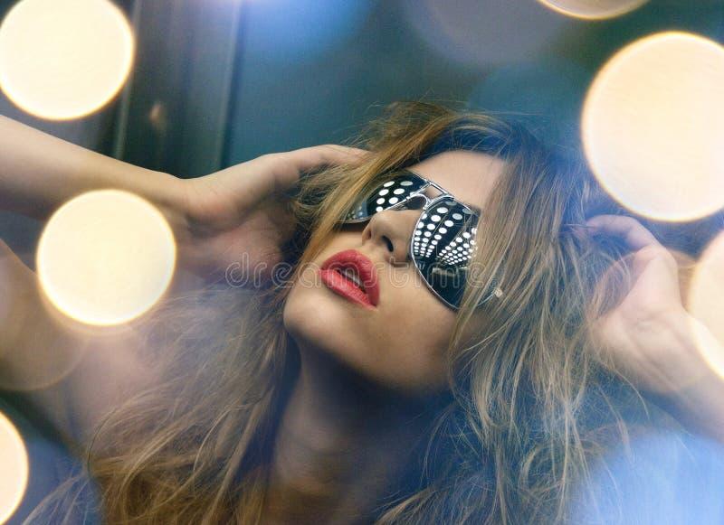 Härlig kvinna i solglasögon i hiss royaltyfri foto
