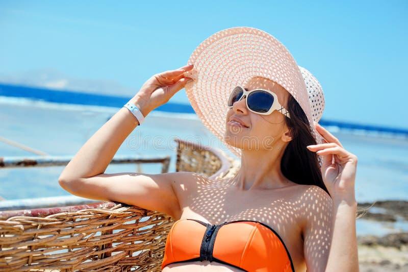 Härlig kvinna i solglasögon och den vita hatten som solbadar på stranden royaltyfri foto