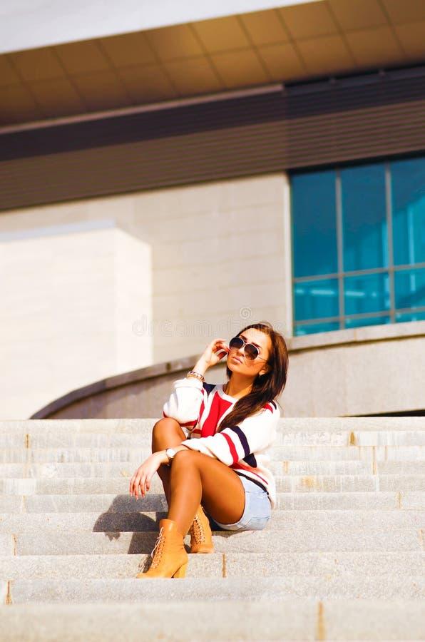 Härlig kvinna i solglasögon som sitter på trappa arkivbild