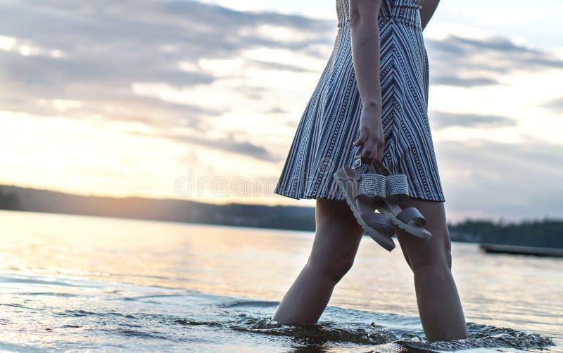 Härlig kvinna i solnedgång som går i vatten och sjön arkivfoto