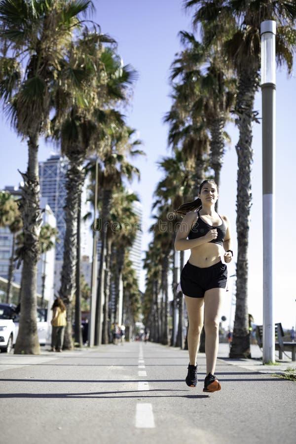 Härlig kvinna i sportkläder som kör på cykelgränden på sjösidan i Barcelona & x28; SPANIEN arkivbilder