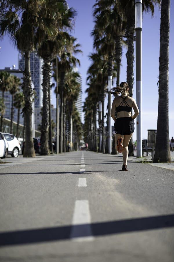 Härlig kvinna i sportkläder som kör på cykelgränden på sjösidan i Barcelona & x28; SPANIEN royaltyfria foton