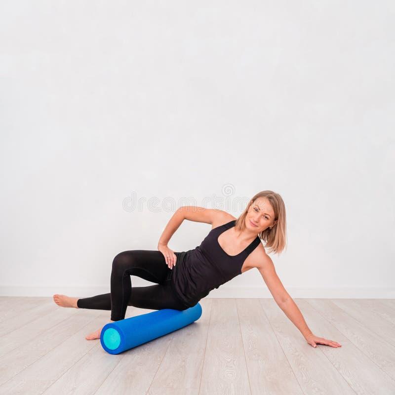 Härlig kvinna i sportswear, Pilates instruktör som sträcker och värmer upp med skumrullen, royaltyfria foton