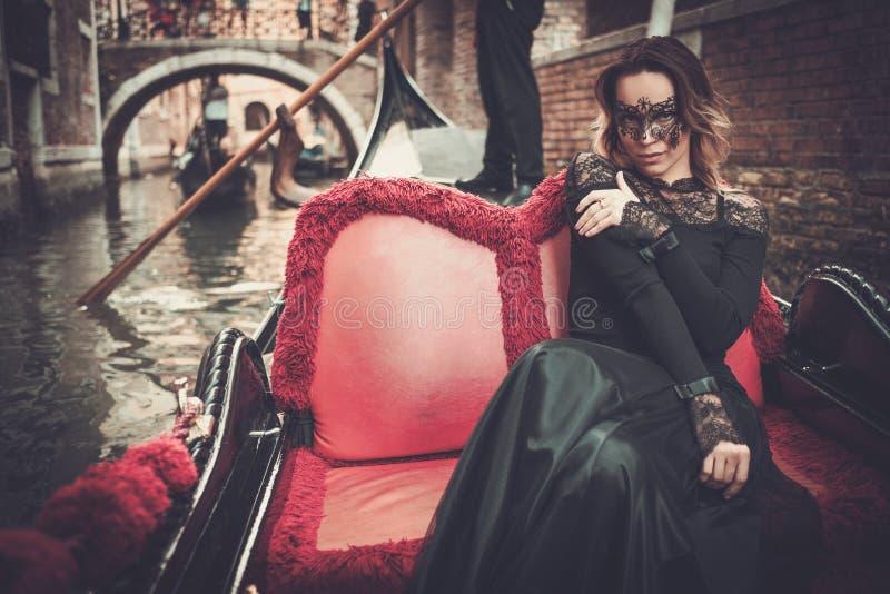 Härlig kvinna i svart klänning med carnaval maskeringsridning på gondolen fotografering för bildbyråer