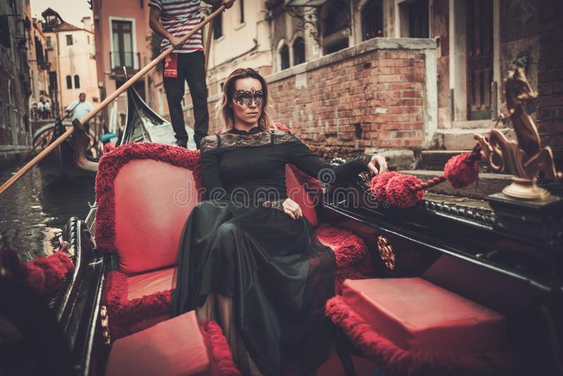 Härlig kvinna i svart klänning med carnaval maskeringsridning på gondolen royaltyfri fotografi