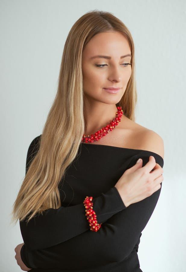 Härlig kvinna i svart klänning med den röda halsbandet och armbandet arkivbilder