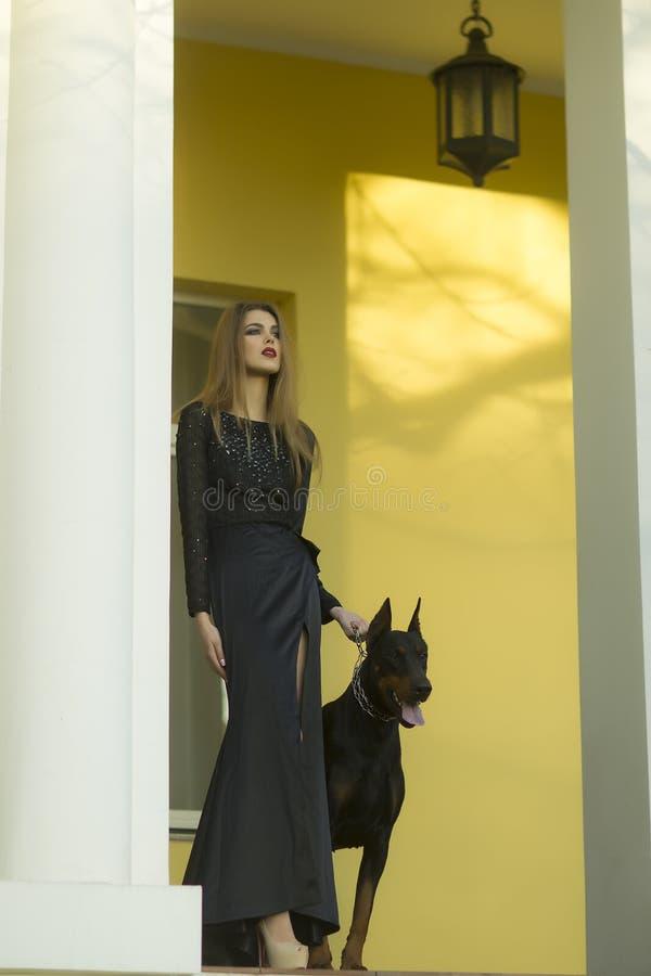 Härlig kvinna i svart klänning med mastiffen royaltyfri bild