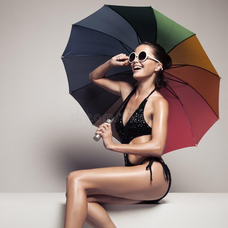 Härlig kvinna i swimwear och solglasögon som rymmer paraplyet royaltyfri foto