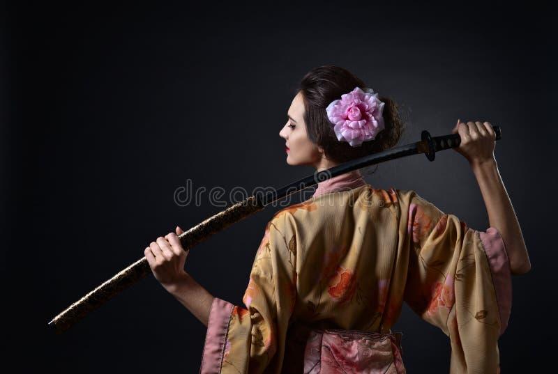 Härlig kvinna i traditionell japansk kimono med katana arkivfoto