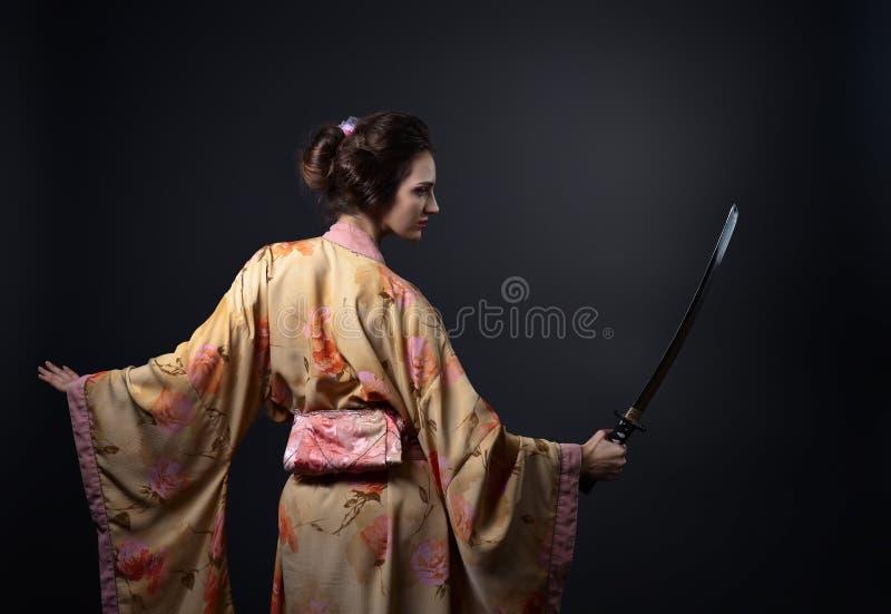 Härlig kvinna i traditionell japansk kimono med katana royaltyfria foton