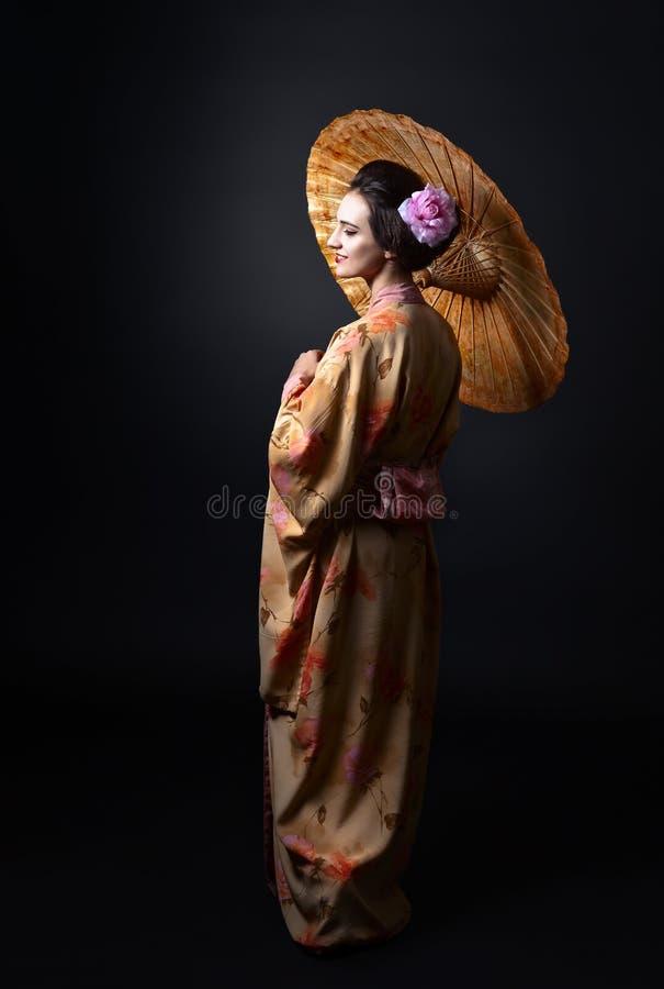 Härlig kvinna i traditionell japansk kimono med paraplyet arkivbild
