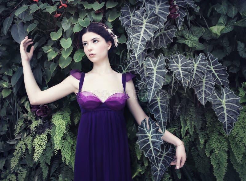Härlig kvinna i tropisk trädgård royaltyfri fotografi