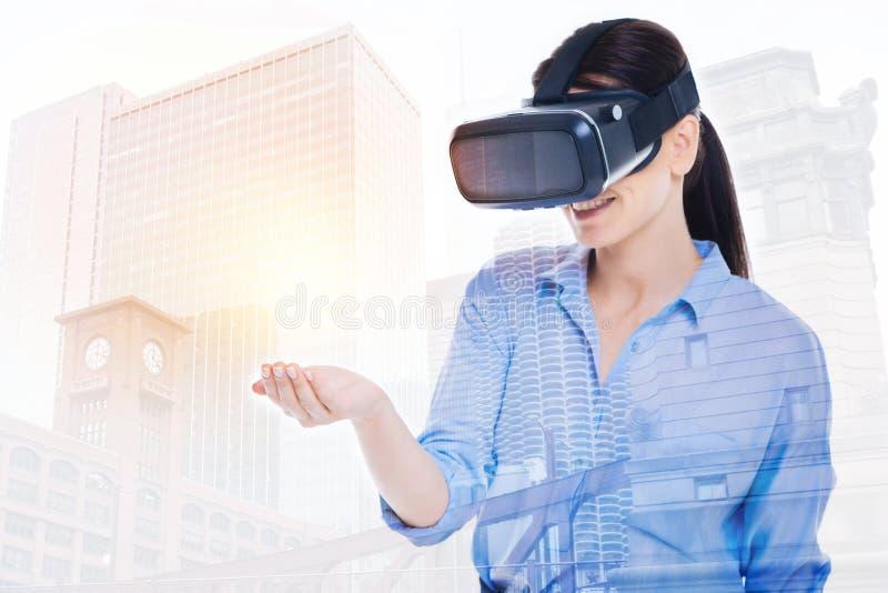 Härlig kvinna i VR-hörlurar med mikrofon som rymmer faktiskt objekt i hand royaltyfri bild