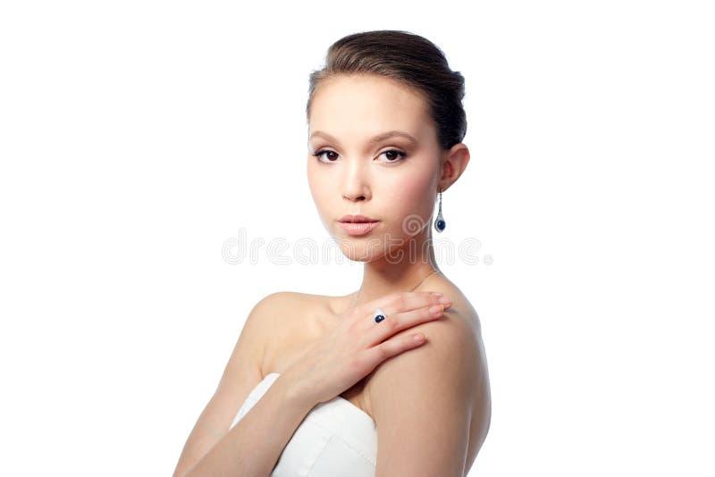 Härlig kvinna med örhänget, cirkeln och hängen arkivfoto