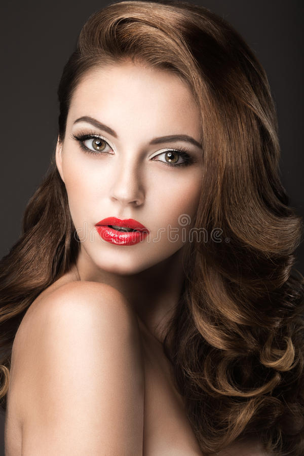 Härlig kvinna med aftonsmink, röda kanter och krullning Härlig le flicka arkivfoton