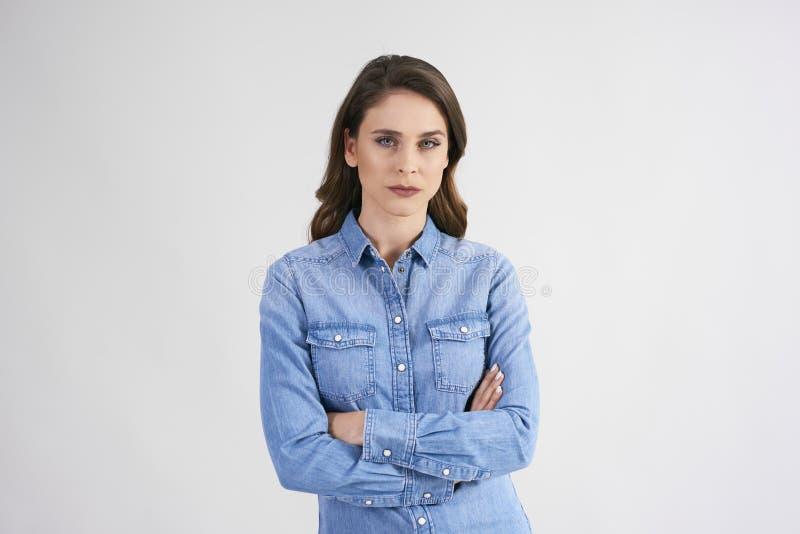 Härlig kvinna med armar som korsas på studioskottet royaltyfri foto