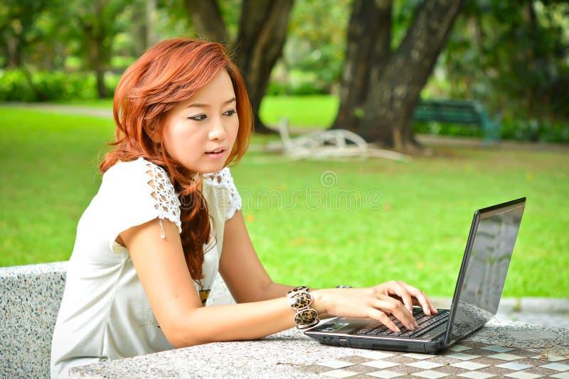 Härlig kvinna med bärbara datorn royaltyfri bild