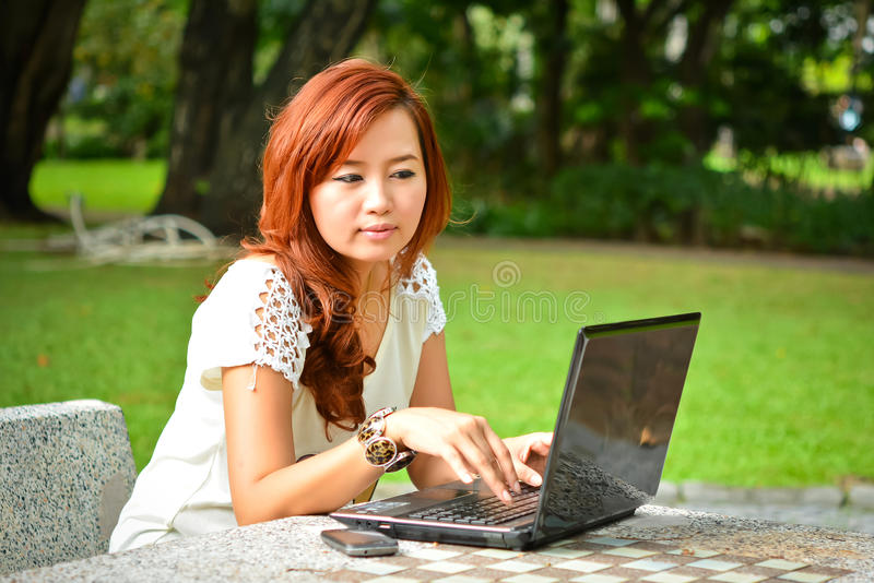 Härlig kvinna med bärbara datorn royaltyfri foto